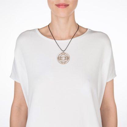 Ramaya symbool ketting van berkenhout op model met wit shirt